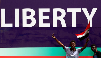 A Sudanese man waves a national flag and makes victory sign in front of a banner in Khartoum