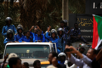 A riot police officer makes a victory sign as others watch while people marching in Khartoum
