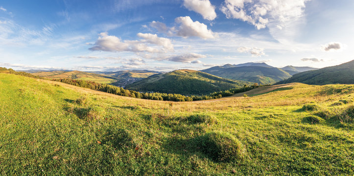 panorama of a countryside in mountains. beautiful early autumn landscape in evening light. grassy meadow on the hill. fluffy clouds above the distant ridge. village down in the valley