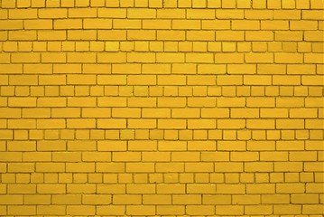 Yellow or auric painted brick wall
