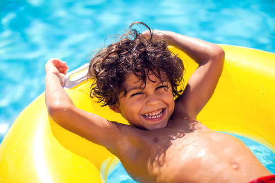 Kid boy swims with inflatable circle in the pool. Children, summer and holiday concept