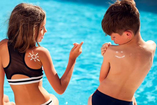 Children with sun protection cream on skin in the pool. Children, summer, holiday and healthcare concept