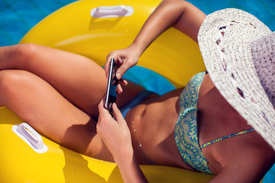Woman spends time and has relax on the pool with phone. People, summer and holiday concept