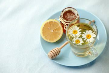 Chamomile flowers and chamomile tea. Chamomile tea in glass teacup with flowers, honey and lemon, top view, prevention of seasona flu colds