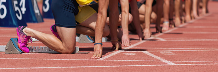 Group of male track athletes on starting blocks.Hands on the starting line.Athletes at the sprint start line in track and field Fototapete