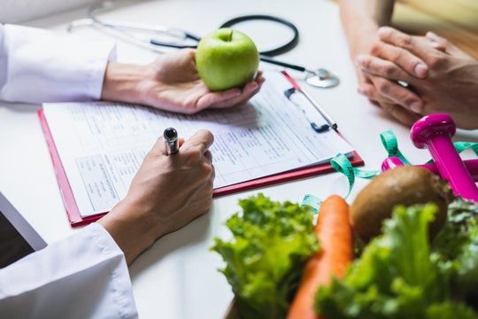 Nutritionist giving consultation to patient with healthy fruit and vegetable, Right nutrition and diet concept