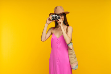 Happy girl in a pink dress and sunglasses holding camera on a yellow background