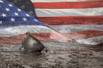 United States Flag with Black and White photo of military helmet on beach in the water.