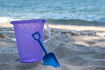 close up of Bucket and shovel in sand with water in the background
