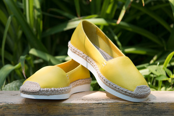 Espadrilles on a background of green grass. A pair of yellow espadrilles on a green background.