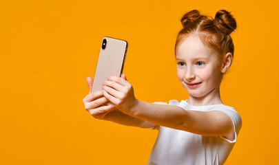 cheerful little red-haired girl taking selfie with mobile phone against a yellow wall.
