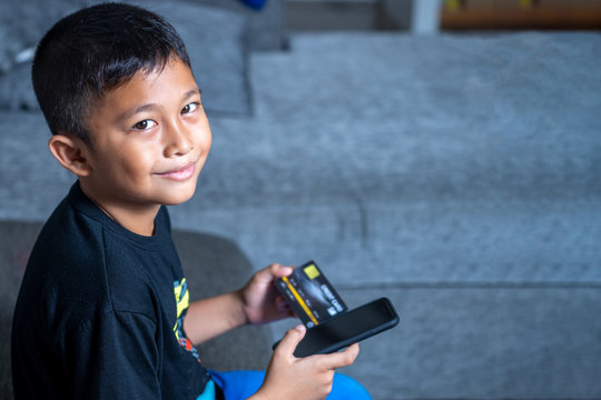 Yong Asian Children age 7-10 Years old with yellow skin, holding black credit card and black mobile phone on the sofa using his parent credit card to buy item online without permission.