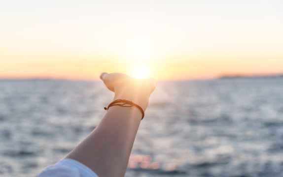 The sun at sunset in the female hand on the background of the sea.