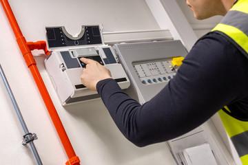 Obraz Male Technician Checking Smoke Detector In Datacenter - fototapety do salonu
