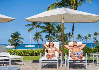 Couple relaxing sun tan at luxury beach hotel resort lying down on loungers by the pool sunbathing together happy. Tropical summer vacation people lifestyle.