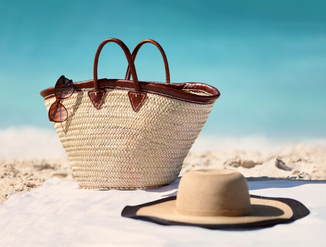 Sun vacation beach winter travel holiday background- Beach bag, fashion hat and sunglasses for Caribbean relaxation. . Copy space on blue ocean. Fashion stylish luxury accessories.