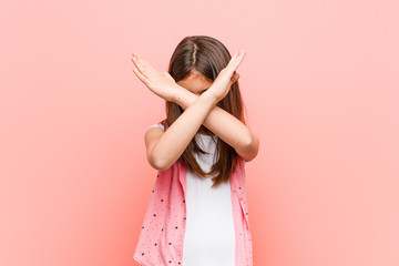 Cute little girl keeping two arms crossed, denial concept. Wall mural