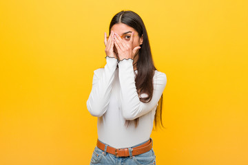 Young pretty arab woman against a yellow background blink through fingers frightened and nervous.