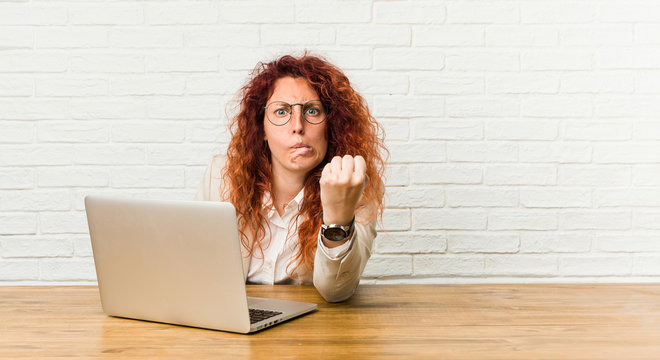 Young redhead curly woman working with her laptop showing fist to camera, aggressive facial expression.