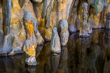 Fotobehang Fantasie Landschap beautiful stalagmite stones in the water of a drip stone cave, nature underground scenery