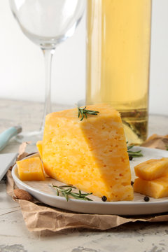 Slices of delicious marble cheese with a sprig of rosemary, honey and a cheese knife and white wine on a plate on a light concrete background.