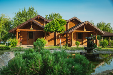 Wooden cottages with log and paved with wild stone paths on the background of green trees and...