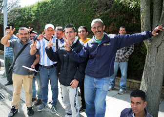 Venezuelans make the victory sign, while they wait for migration documents in front of the Chile Consulate in La Paz