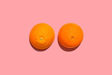 Breasts Concept, Orange Citrus Fruit Against Pink Background