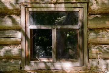 Old window in an abandoned log house on a sunny summer day