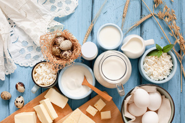 Different types of dairy products on blue wooden background: milk, sour cream, cottage cheese, cheese, cream, yogurt, eggs and butter top view with copy space