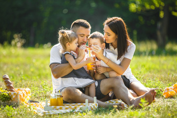 Cheerful family having picnic. Parents having dinner with their kids outdoors.