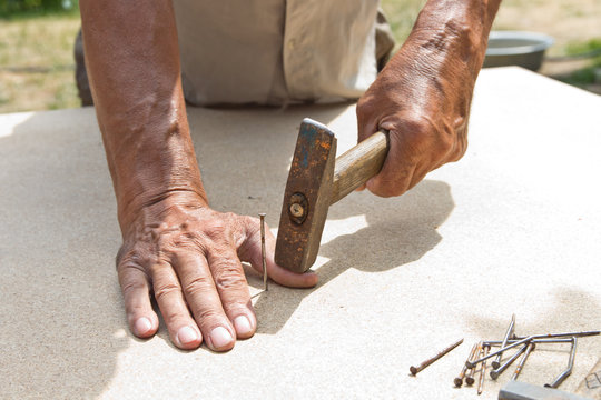 The man hit his finger with a hammer. Professional carpentry, woodwork and people. concept of injury in the workplace