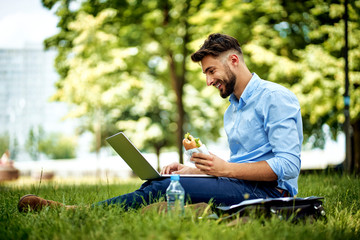Young cheerful businessman sitting in the park with sandwich and laptop Fotomurales