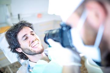 Fotografo odontoiatra per la fotografia della dentatura d un paziente sdraiato sulla poltrona.