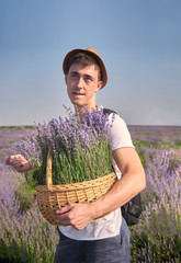 a man stands with a big basket of lavender and makes fun