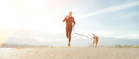 Jogging man with his dog in the morning. Active healthy lifestyle concept image.