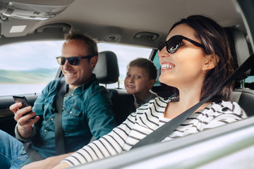Happy family auto traveling concept image. Car interior view of female driving, man dealing mobile phone and little son smiling into camera