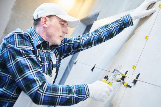 Tiler installing large format tile on wall. tile leveling system