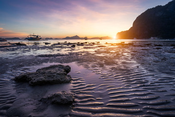 Tropical beach in ebb time low tide on sunset. Mudflats and sun reflections at the golden hour. mountain chain isles at horizon. Coron Corong beach, El Nido, Phillipines Wall mural