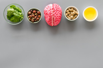 Brain food concept with peanut, hazelnut, seed-oil, spinage on gray background top view copyspace