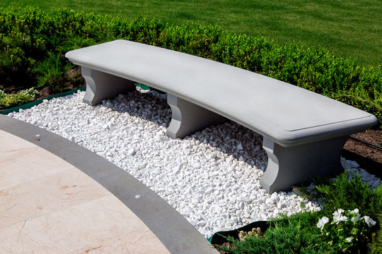 stone gray bench strewn with white stone pebbles in a garden with boxwood bushes and a green lawn with plants, close up of a place for sitting and resting near a marble tile walkway on a sunny summer.