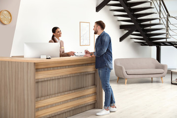 Professional receptionist working with client at desk in modern hotel