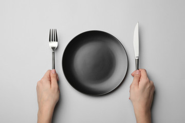 Woman with fork, knife and empty plate on grey background, top view Wall mural