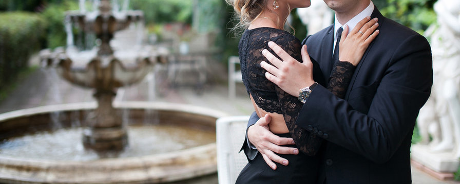 Elegant man in a black suit and Rich woman in black dress hug. Young stylish man and woman in beautiful backyard with fountain on background.