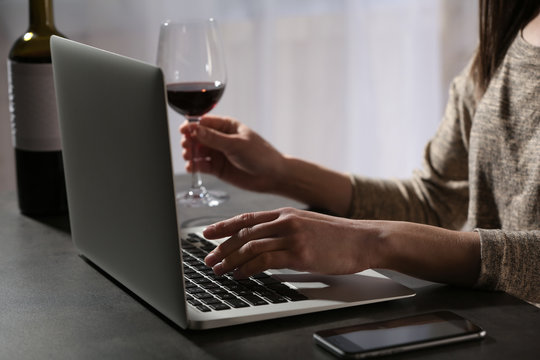 Woman with glass of wine using laptop at table indoors, closeup. Loneliness concept