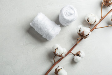 Flat lay composition with cotton rolls and flowers on grey stone background