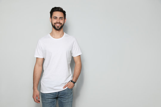 Young man in t-shirt on light background. Mock up for design