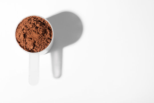 Scoop of protein powder on white background, top view
