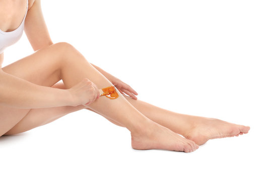Woman doing leg epilation procedure with hot wax isolated on white, closeup
