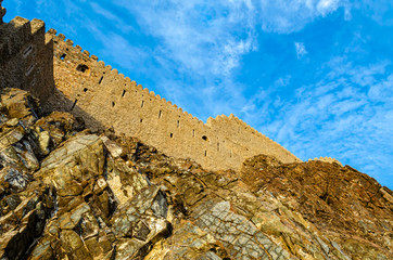 Muttrah fort wall on the rocky hill with blue sky background. Shot from below in Muscat,Oman.